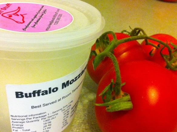 Buffalo mozzarella in brine next to tomatos on the vine