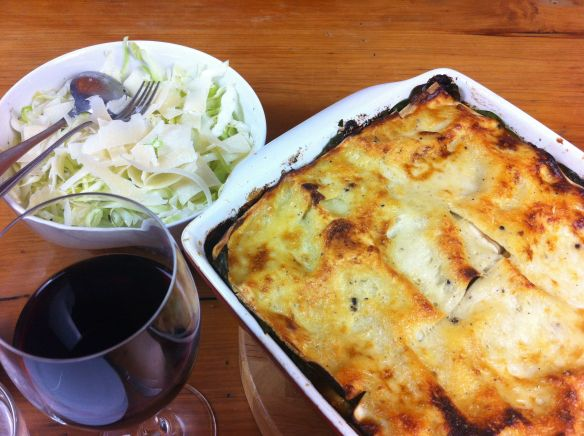Beef mushroom and spinach lasagne on the table with wine and salad