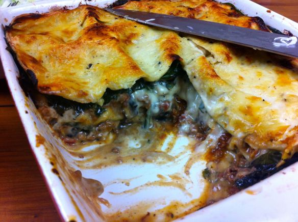 Beef, mushroom and spinach lasagne with a piece cut out