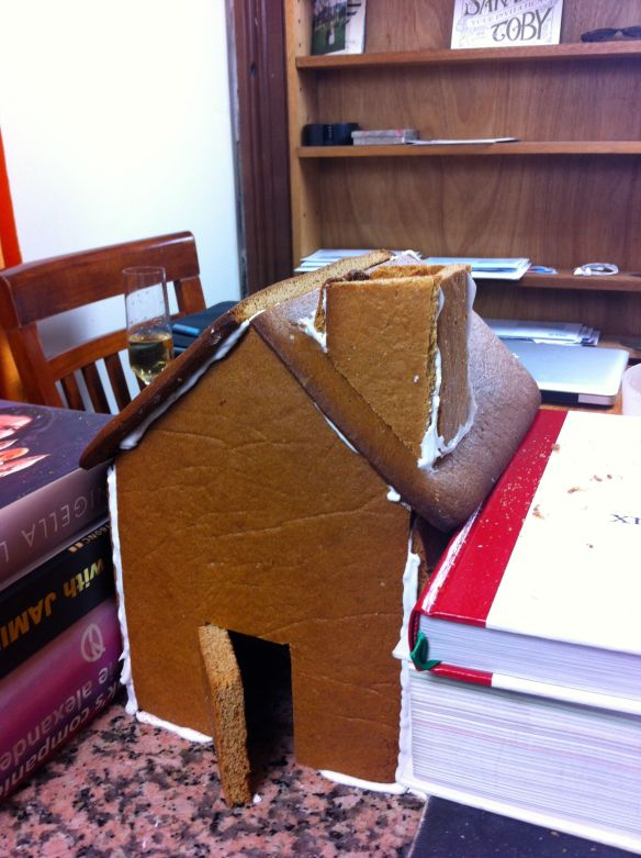 gingerbread house construction completed and supported either side by books