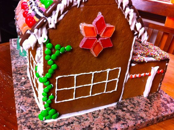 back side of the gingerbread house with a window, ski rack and creeping vine