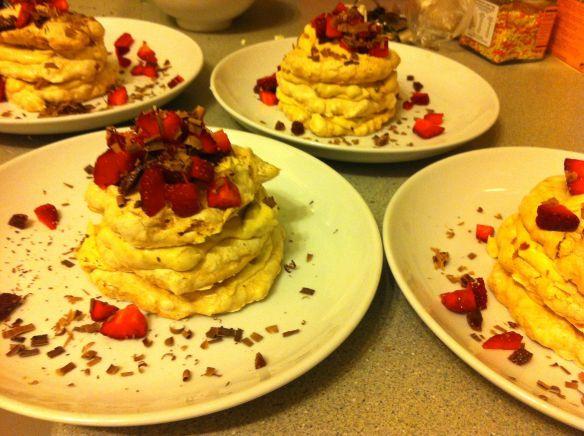 four hazelnut meringue stacks on plates