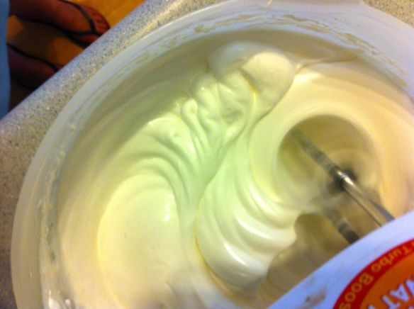 mixing meringue mixture with hand beater