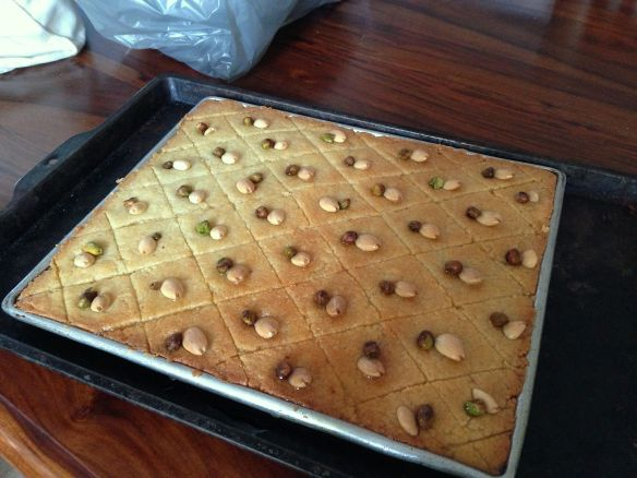 semolina slice in a tray with almonds and pistachios